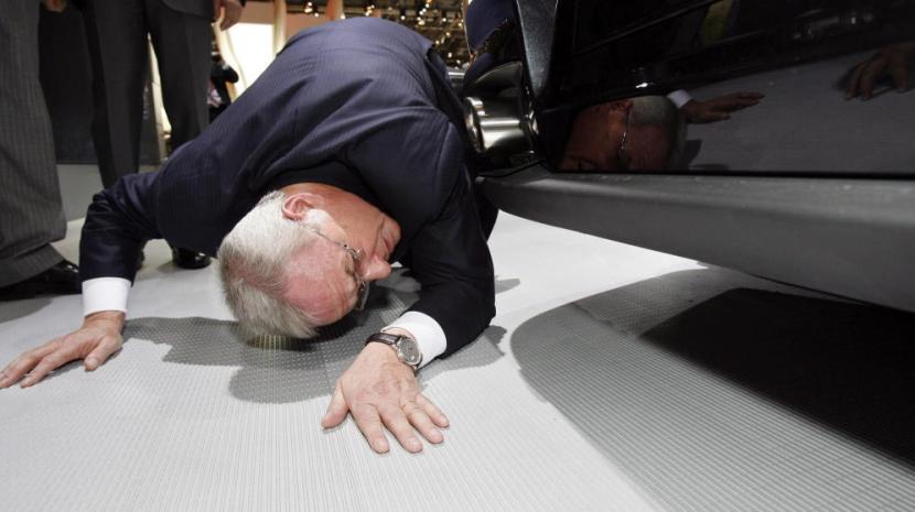 El presidente de Volkswagen AG, Martin Winterkorn, mientras se agacha para (supuestamente) ver los bajos de un Porche. En realidad, se está partiendo la caja. /EFE